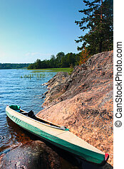 Canoe on the lake shore - Canoe at camp on the shore of the...