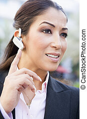 Businesswoman using bluetooth earpiece outside