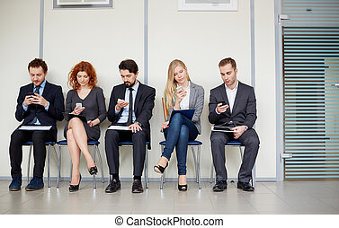 People with mobile phones - Row of several business partners...