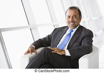 Businessman relaxing in lobby - Business relaxing in office...