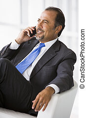 Businessman talking on mobile phone in lobby