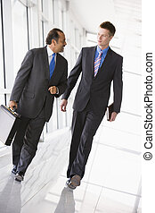 Businessmen walking through lobby - Businessmen walking...
