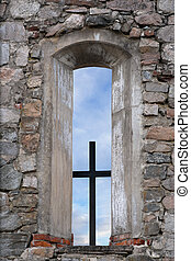 cross in window of ancient stone church - metal cross in...