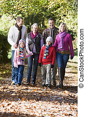 Multi-generation family walking through woods -...