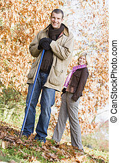 Couple clearing autumn leaves from garden