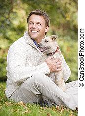 Man sitting outside holding dog - Man sitting outside...