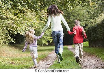 Mother and children running along woodland path - Mother and...