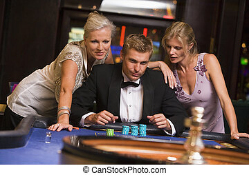 Man with glamorous women in casino