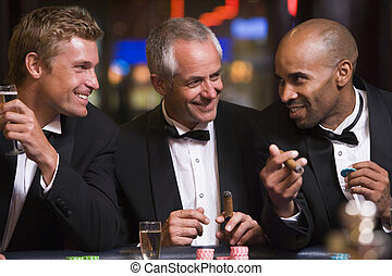 Three men gambling at roulette table in casino