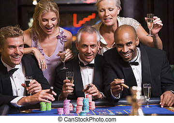 Group of friends gambling at roulette table in casino