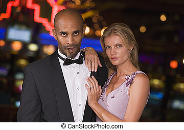 Couple standing inside casino - Glamorous couple standing...