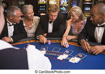 Group of friends playing blackjack in casino - Five people...