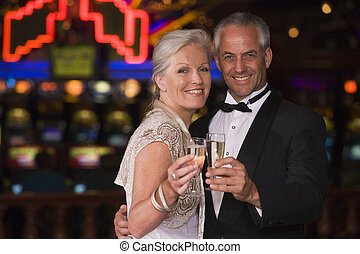 Mature couple celebrating in casino - Mature couple...