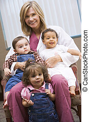 Consultant with three IVF toddlers - Consultant holding...