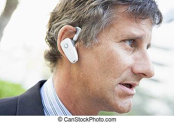 Businessman wearing earpiece outdoors