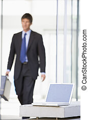 Laptop sitting in office lobby with businessman walking in