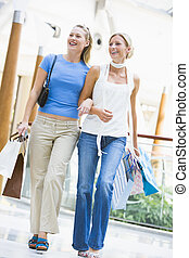 Two friends shopping in mall carrying bags