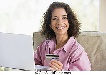 Woman making online purchase at home looking to camera