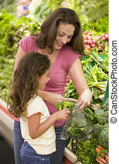 Mother and daughter in produce section - Mother and daughter...