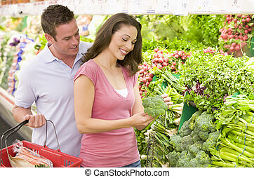 Couple shopping in produce section - Couple shopping in...
