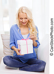 smiling woman with gift box at home