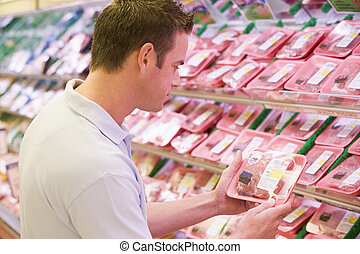 Man buying fresh meat from supermarket