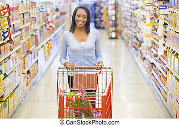 Woman pushing trolley in supermarket - Woman pushing trolley...