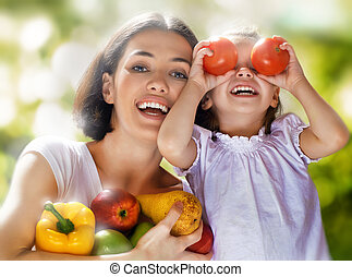 eating healthy food - happy family keeps fresh vegetables