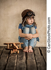 Sad child with toy wooden airplane sitting on the floor