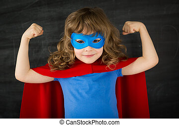 Superhero kid against school blackboard