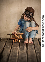 Sad child playing with airplane - Sad child playing with toy...
