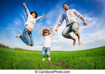 Happy family jumping in green field against blue sky Summer...