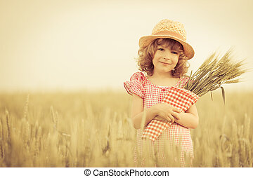 Happy child holding wheat in summer field
