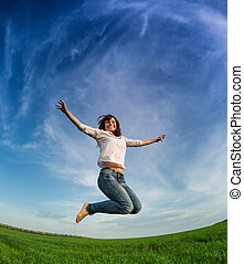 Happy woman jumping in green field against blue sky Summer...