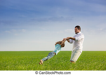 Father and child having fun outdoors in spring field against...