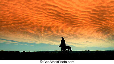 man walking dog silhouetted against red sky