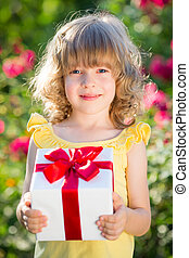 Mother`s day - Child holding gift box against green...