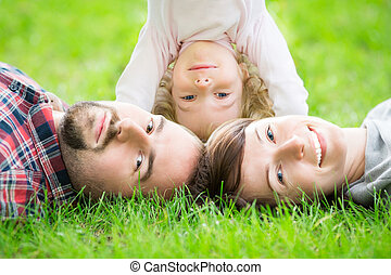 Happy family in spring - Happy family lying on green grass...