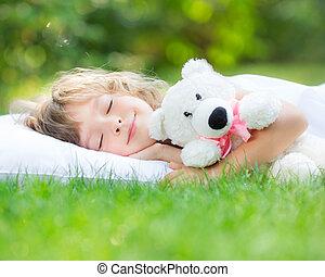 Child sleeping in spring garden