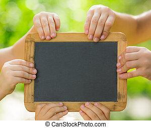 Blackboard blank in hands - Many hands holding blackboard...