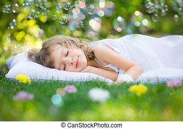 Kid sleeping in spring garden - Happy kid sleeping on green...