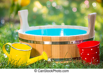 Wooden vat outdoors - Wooden vat, watering can and bucket on...