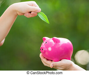 Piggybank and leaf in hands against green spring background