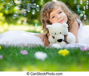Child lying on grass - Happy child with toy teddy bear on...