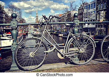 Old bicycle on bridge Amsterdam cityscape at sunny day