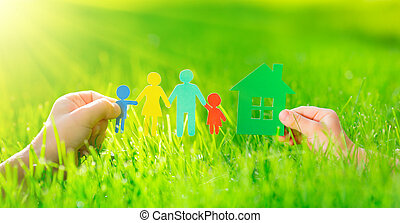 Paper house and family in hands over spring green grass....