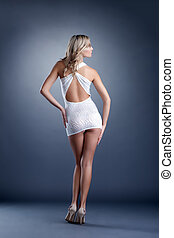 Slender girl posing in short dress, back to camera - Image...