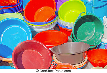 Many plastic basins in different colors, as a stack on a...