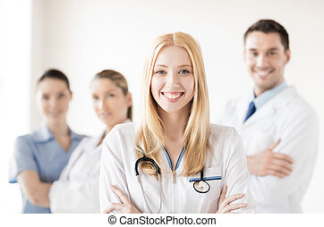 female doctor in front of medical group - healthcare and...
