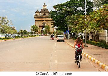 Young woman riding bike near Victory Gate Patuxai, Vientiane, Laos, Southeast Asia